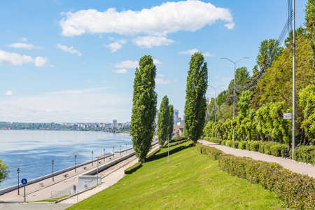 A deserted embankment on a spring or summer day. Clouds in a blue sky. The Volga River in the background, the city of Saratov, Russia