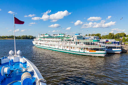 Two three-deck passenger ships at the berth in the city of Kazan. Volga River, Republic of Tatarstan, Russia. Shooting from the ship. A sunny summer day. 스톡 콘텐츠