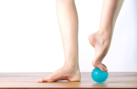 ballet dancer massage the forefoot with a ball Stock Photo