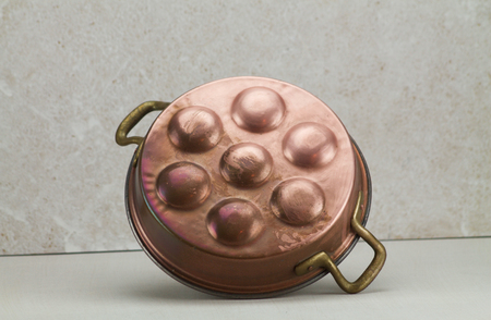 oxidized: old  copper pot for eggs on sponged white background Stock Photo