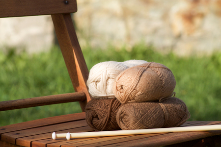 balls of wool in shades of natural tones on a wooden chair Stock Photo