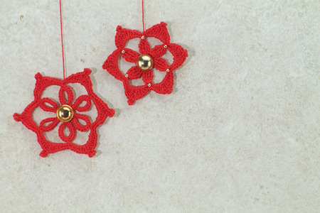 sponged: two red crochet christmas stars with golden button on sponged white background Stock Photo