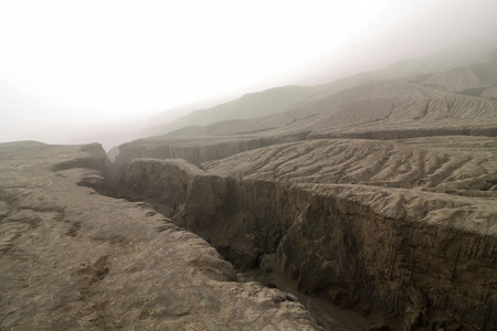 crack climbing: cracks on the bromo volcano surface, early morning in the fog Stock Photo