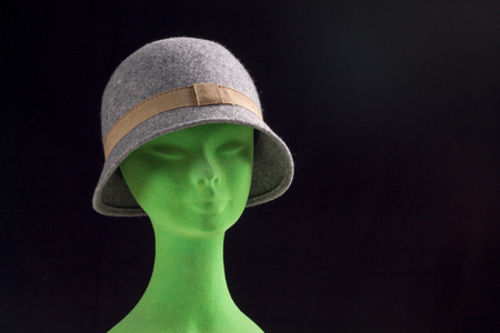 grey female hat on mannequin head, space for text