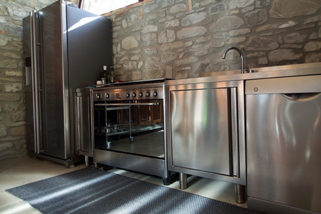 modersteel  kitchen  with large fridge and dishwasher in rustic interior