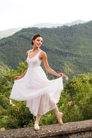 prachtige balletdanseres met romantisch wit kostuum als bruid in de natuur Stockfoto