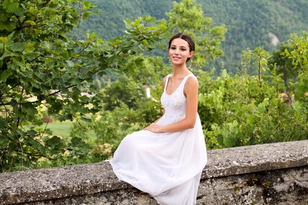 自然の中でロマンチックな白いドレスの石の壁の上に座って美しい若い女性