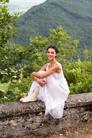 portret van mooie balletdanser zittend op stenen muur met witte jurk en pointe schoenen Stockfoto