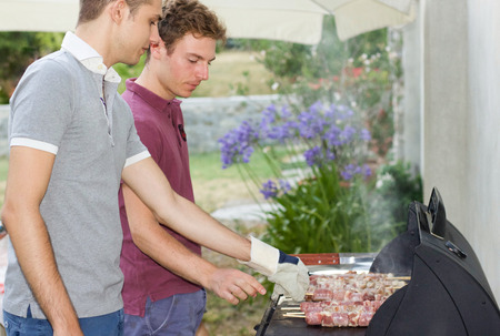 two boys cook meat skewers on barbecue in the garden for a friends dinner Stock Photo