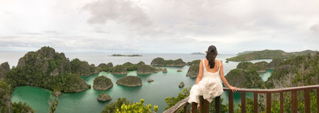 young woman sitting on a terrace looking the famous panorama of pyanemo rocks,Raja ampat west papua Stock Photo