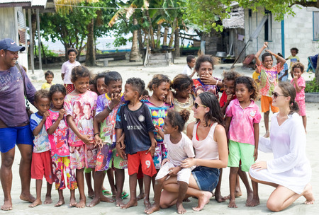 WEST PAPUA, RAJA AMPAT - August 28, 2017:  group of asian children interacting with two european girls in Fam island, west papua