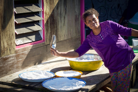 WEST PAPUA, RAJA AMPAT - August 24, 2017: local woman works in front of her home with bowls of salt smiling to tourists Editorial