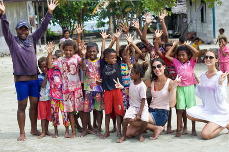 WEST PAPUA, RAJA AMPAT - August 28, 2017:  group of asian children interacting with two european girls in Fam island, Raja Ampat archipelago Editorial