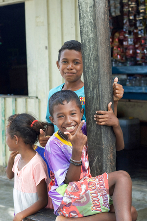 WEST PAPUA, RAJA AMPAT - August 28, 2017 :  group of unidentified asian indigenous children in a street of local village smiling and interacting with tourists, Raja ampat archipelago Raja ampat archipelago