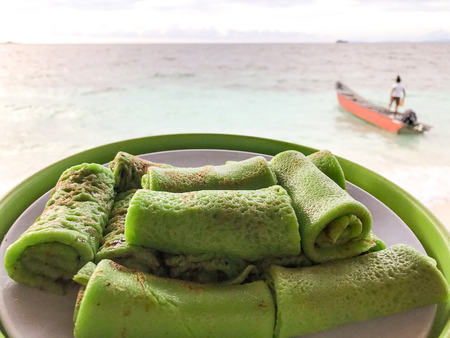 delicious rolled up pancakes with chocolate served as breackfast on the beach, raja ampat