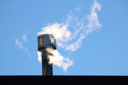 white smoke comes out of a house chimney, blue sky background and copy space