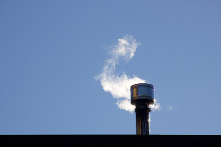 white smoke coming  out of a  metallic chimney, blue sky background