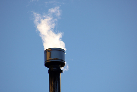white smoke coming out upwards from a metallic chimney