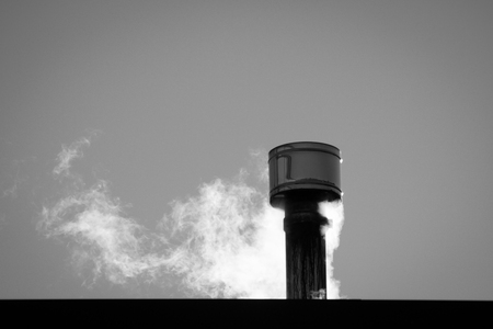 close up of smoke coming out from a chimney, black and white
