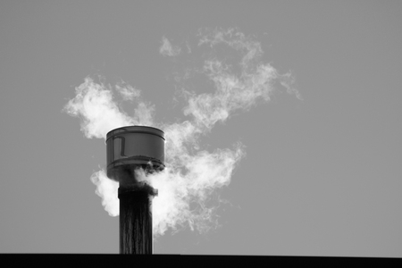 close up of white smoke coming out from a chimney, copy space Stock Photo