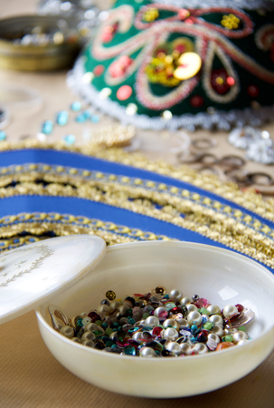 mix of multicolored pearls and beads in a vintage white bowl
