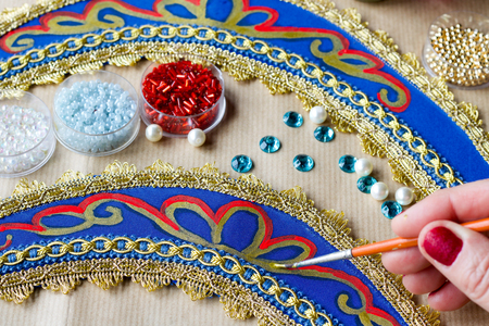 hand with brush decorating an homemade folk russian tiara with gold color