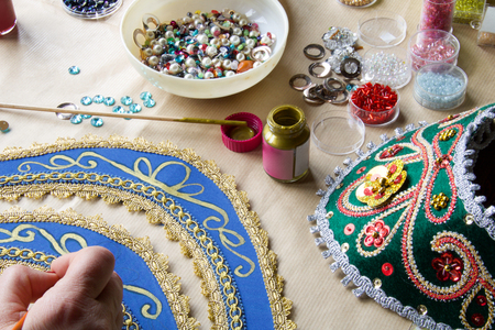 hand with brush make decorations on fabric with golden color to make a russian folk tiara