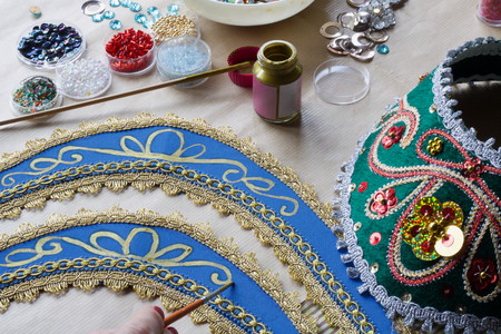hand with brush and gold color make decorations on a  homemade folk russian tiara Stock Photo