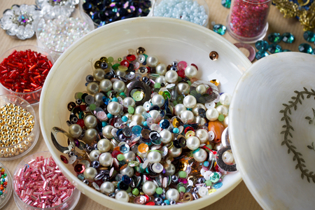 close up of multicolored vintage pearls and beads in small boxes