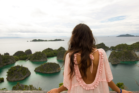 young woman back in summer dress looking exotic panorama, west papua Stock Photo