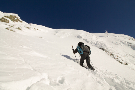 hiker with snowshoes go higher to the top of mountain in the  fresh snow