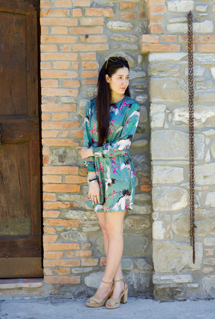 full length portrait  outdoors of young trendy girl near a rustic stone wall Stock Photo