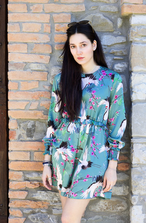 portrait of trendy brunette young woman standing near a stone wall in colorfu dress
