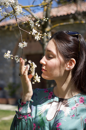 close portrait of fashion girl in the garden caressing plum tree flowers in a sunny day