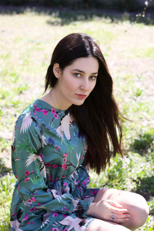 young  fashion brunette with fantasy dress chin in the grass in a sunny day of spring