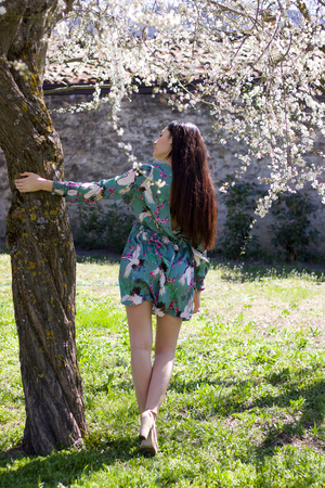 pretty girl in fantasy dress full lengh back in a garden embracing a plum tree in bloom