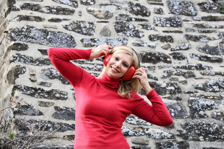 beautiful  blond woman in red sweater smiling listening music with headphone Stock Photo