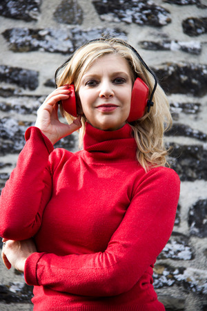 portrait of blond woman in red sweater with red earmuffs on stone wall background Stock Photo