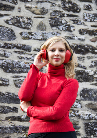 blond woman with red earmuffs smiling near a stones wall contruction Stock Photo