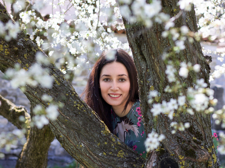 beautiful young woman portrait smiling happy between branches of tree in bloom, concept of purity