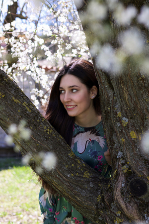 portrait of beautiful woman looking through the branches of a tree in bloom smiling