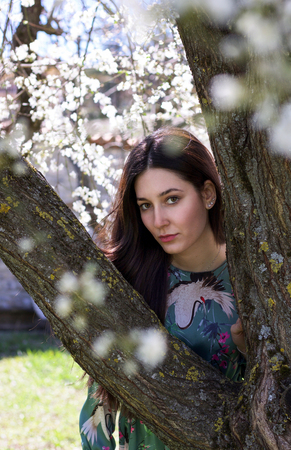 young model  looking intensely in camera near a tree in bloom in springtime Stock Photo