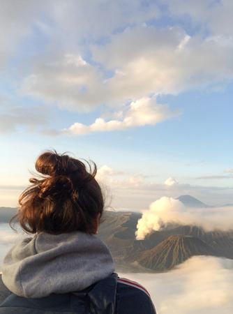 young woman back looking an amazing panorama of bromo volcano caldera, tengger national park Java island