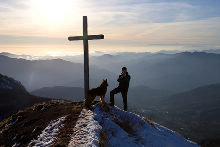 hiker doing a self portrait on the top of the mountain with his dog, sunset on ligurian sea Stock Photo