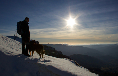 hiker with a dog looking the horizon from the top of the mountain at sunset on ligurian sea