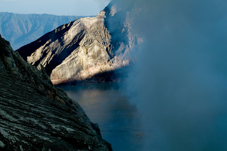 the sunrise on kawah ijen volcano  crater in the middle of smoke coming out from solfataras