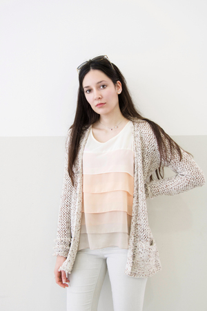 Beautiful young woman in fashionable knitted beige cardigan stands against a double color wall posing