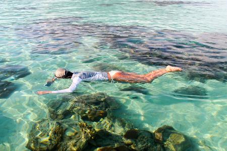 woman enjoying  the snorkeling with a water proof camera, in Koh Lipe island beautiful reef