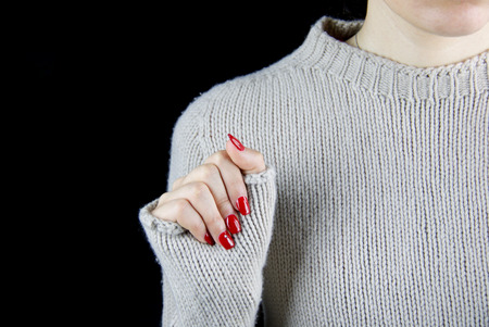 details of cashmere sweater pattern worn by a girl with red nails, black background