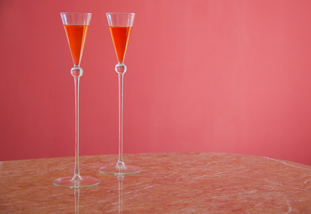 two orange cocktails on a table  in tall glasses isolated on pink background Stock Photo